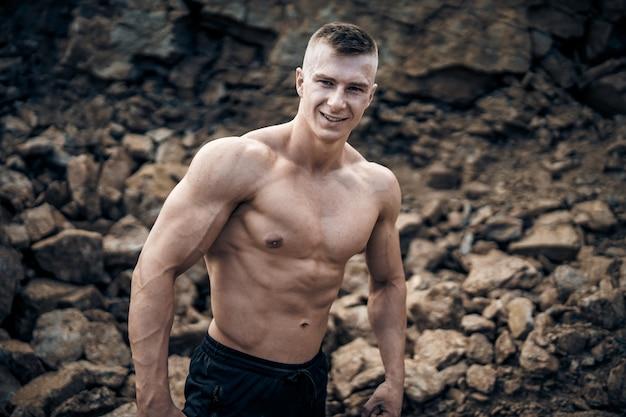 Bel homme avec de gros muscles, posant devant la caméra dans une carrière. portrait d'un bodybuilder souriant. fermer.