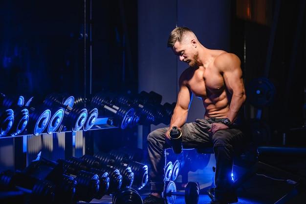 Bel homme avec de gros muscles, posant devant la caméra dans la salle de gym, fond noir et bleu. portrait d'un bodybuilder souriant. fermer.
