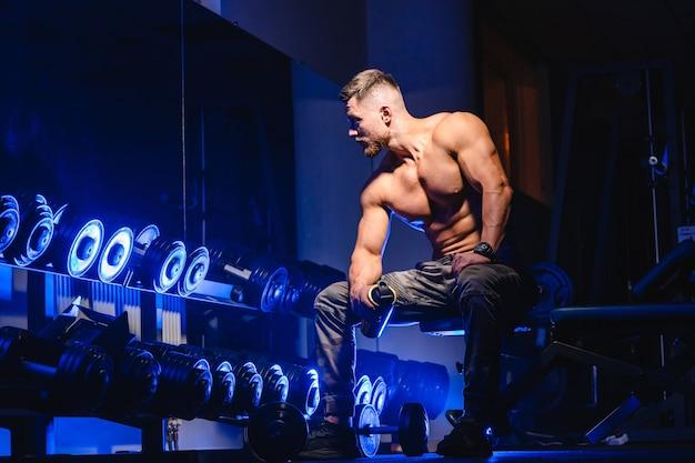 Bel homme avec de gros muscles, posant devant la caméra dans la salle de gym. fond noir et bleu. portrait d'un culturiste. fermer.