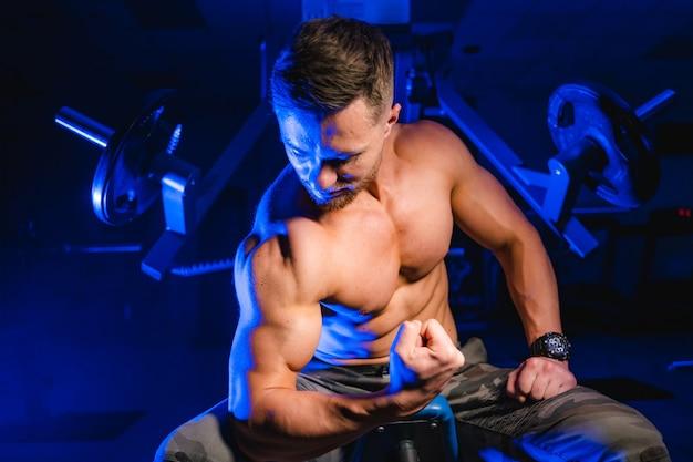 Bel homme avec de gros muscles, posant devant la caméra dans la salle de gym. fond noir et bleu. portrait d'un homme athlétique. fermer.