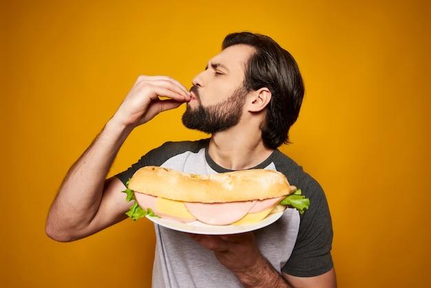 Bel homme avec gros sandwich fait un geste délicieux.