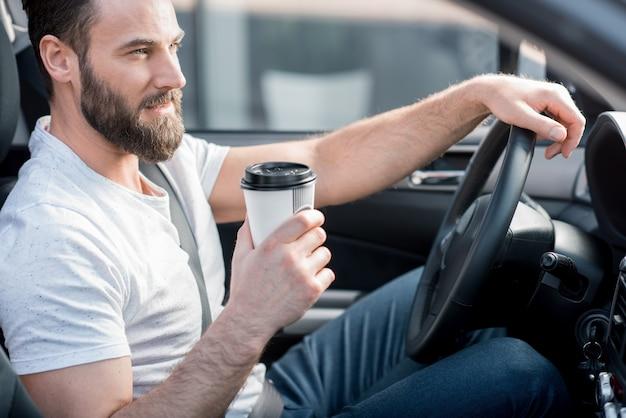 Bel homme habillé en t-shirt blanc décontracté au volant d'une voiture avec du café à emporter