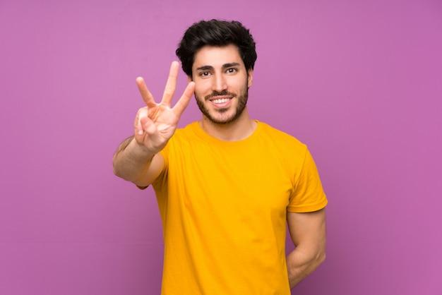 Bel homme heureux et comptant trois avec les doigts