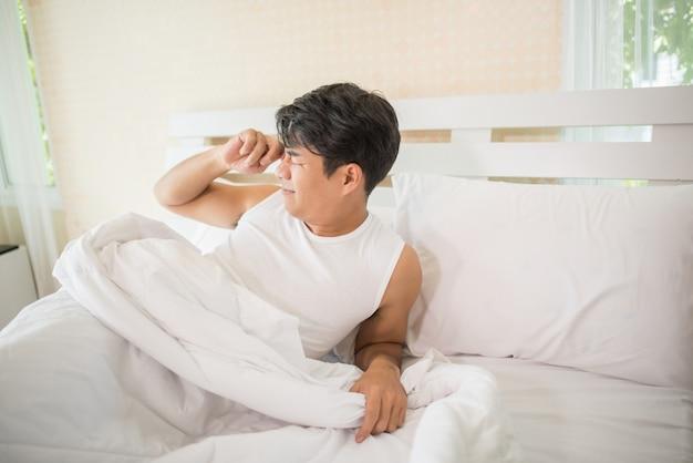 Bel homme heureux se réveiller dans le lit