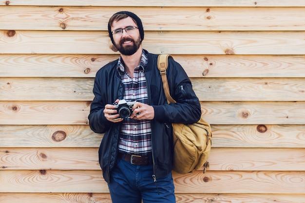 Bel homme hipster avec barbe, chapeau élégant et lunettes posant avec appareil photo rétro en mains