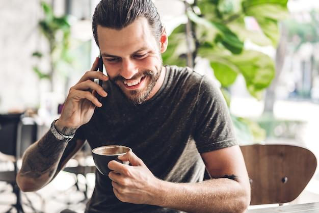 Bel homme hipster barbu utilise smartphone avec café à table au café