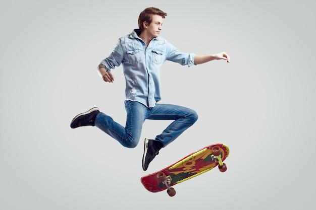 Bel homme hipster en veste de jean faisant le flip sur skateboard élégant