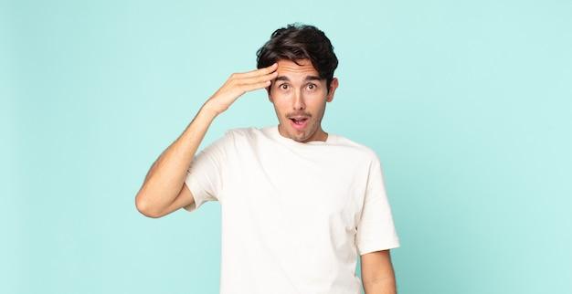 Bel homme hispanique à l'air heureux, étonné et surpris, souriant et réalisant de bonnes nouvelles incroyables et incroyables