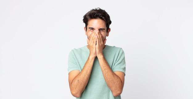 Bel homme hispanique à l'air heureux, joyeux, chanceux et surpris couvrant la bouche avec les deux mains