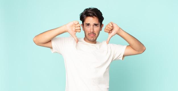 Bel homme hispanique à l'air triste, déçu ou en colère, montrant les pouces vers le bas en désaccord, se sentant frustré