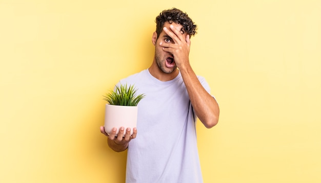 Bel homme hispanique ayant l'air choqué, effrayé ou terrifié, couvrant le visage avec la main. concept de plante décorative
