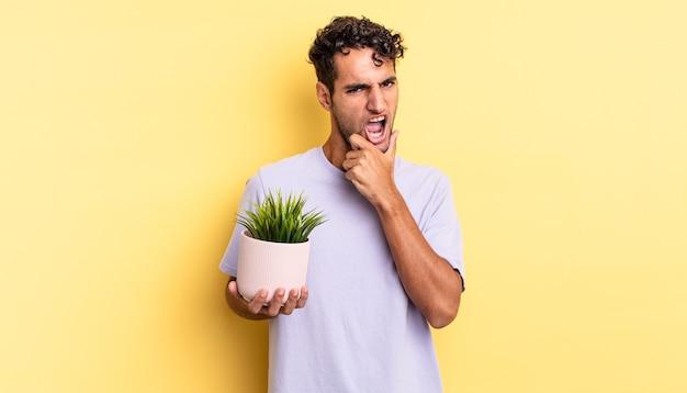 Bel homme hispanique avec la bouche et les yeux grands ouverts et la main sur le menton. concept de plante décorative