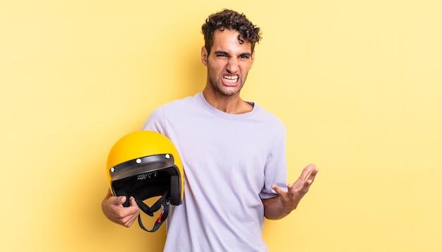 Bel homme hispanique à la colère, agacé et frustré. concept de casque de moto