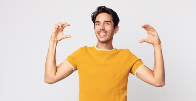 Bel homme hispanique encadrant ou décrivant son propre sourire avec les deux mains, l'air positif et heureux, concept de bien-être