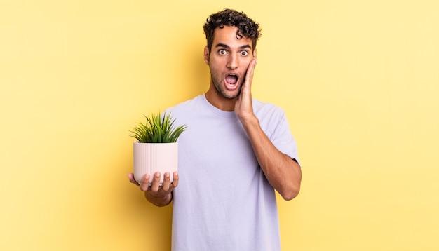 Bel homme hispanique se sentant choqué et effrayé. concept de plante décorative