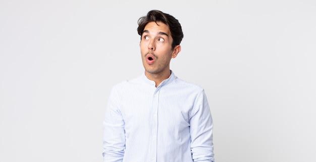 Bel homme hispanique se sentant choqué, heureux, étonné et surpris, regardant sur le côté avec la bouche ouverte