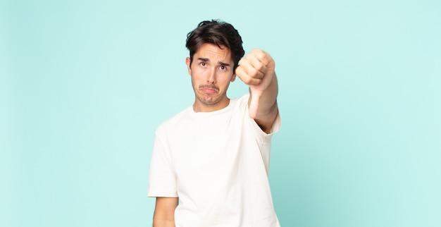 Bel homme hispanique se sentant fâché, en colère, agacé, déçu ou mécontent, montrant les pouces vers le bas avec un regard sérieux