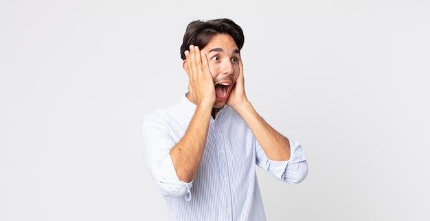 Bel homme hispanique se sentant heureux, excité et surpris, regardant de côté avec les deux mains sur le visage
