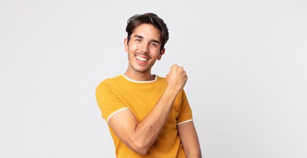 Bel homme hispanique se sentant heureux, positif et réussi, motivé face à un défi ou célébrant de bons résultats