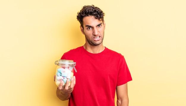 Bel homme hispanique se sentant perplexe et confus. concept de bonbons