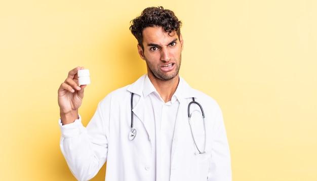 Bel homme hispanique se sentant perplexe et confus. concept de pilules de bouteille de médecin