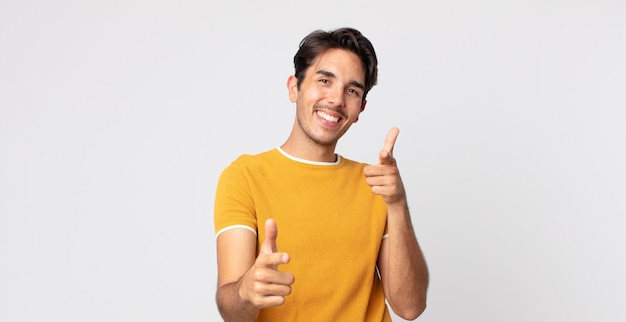 Bel homme hispanique souriant avec une attitude positive, réussie et heureuse pointant vers la caméra, faisant un signe d'arme avec les mains