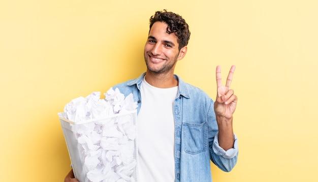 Bel homme hispanique souriant et ayant l'air heureux, gesticulant la victoire ou la paix. concept de poubelle de boules de papier
