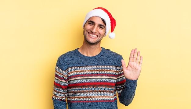 Bel homme hispanique souriant joyeusement, agitant la main, vous accueillant et vous saluant. notion de noël