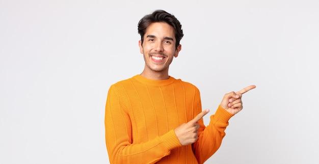 Bel homme hispanique souriant joyeusement et pointant vers le côté et vers le haut avec les deux mains montrant l'objet dans l'espace de copie