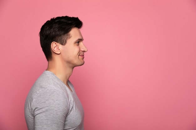 Bel homme. un homme séduisant dans un t-shirt gris, debout de profil et souriant.