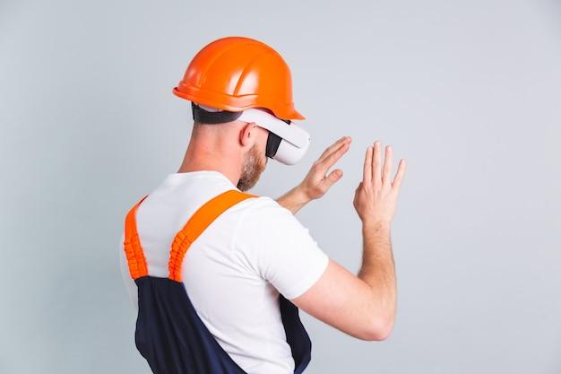 Bel homme ingénieur dans la construction d'un casque de protection et de lunettes vr sur un mur gris touchant l'air