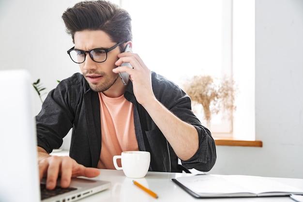 Bel homme inquiet sérieux à lunettes parlant par smartphone et utilisant un ordinateur portable tout en travaillant près de la table au bureau