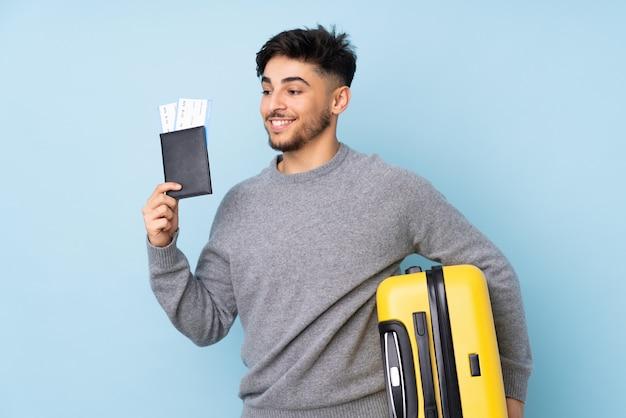 Bel homme isolé sur bleu en vacances avec valise et passeport