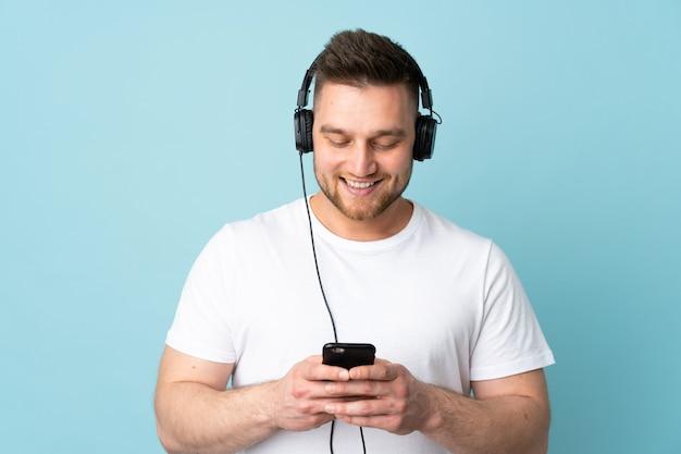 Bel homme isolé sur le mur bleu, écouter de la musique et regarder vers mobile