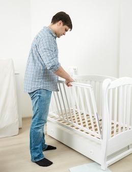Bel homme en jeans et chemise assemblage lit bébé