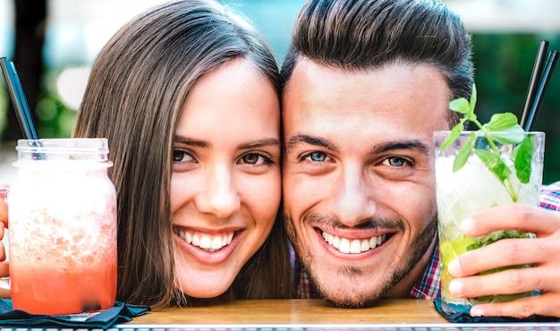 Bel homme et jeune femme souriante sur happy hour au bar à cocktails