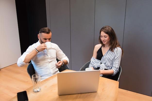 Bel homme et jolie dame buvant du café aromatique et discutant d'un projet commun au bureau