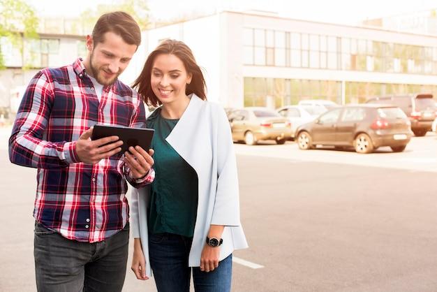 Bel homme et jolie femme regardant tablette numérique debout dans la rue