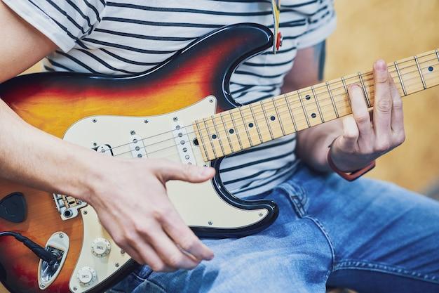 Bel homme jouant de la guitare en studio