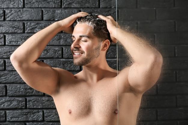 Bel homme lavant les cheveux sur une surface sombre