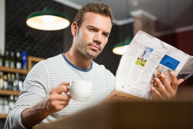 Bel homme lisant un journal et prenant un café