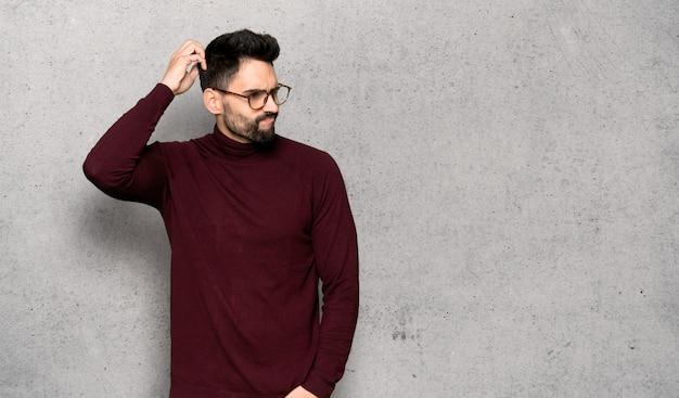 Bel homme avec des lunettes ayant des doutes tout en se gratifiant la tête sur un mur texturé