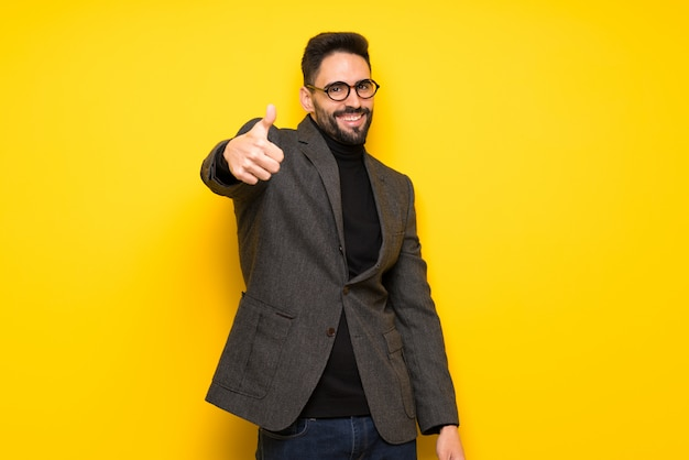 Bel homme avec des lunettes faisant un geste pouce en l'air parce que quelque chose de bien est arrivé