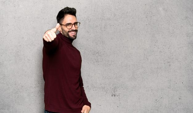 Bel homme avec des lunettes faisant un geste pouce en l'air parce que quelque chose de bon est arrivé sur le mur texturé