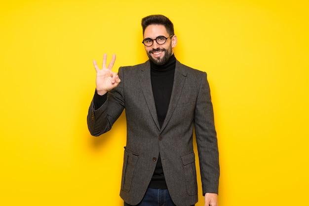 Bel homme avec des lunettes heureux et comptant trois avec les doigts