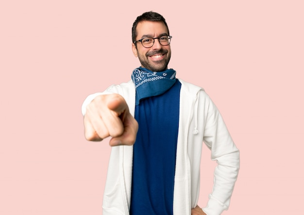 Bel homme avec des lunettes pointe le doigt vers vous avec une expression confiante sur fond rose isolé