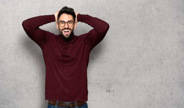 Bel homme avec des lunettes prend les mains sur la tête car migraine sur mur texturé