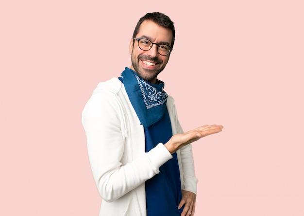 Bel homme avec des lunettes présentant une idée tout en regardant souriant vers sur fond rose isolé