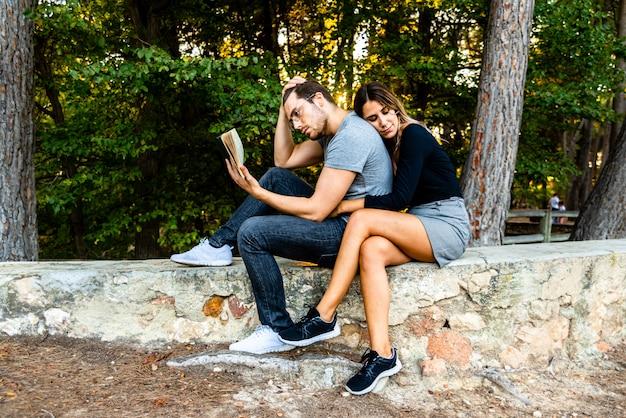 Bel homme à lunettes séduit la jeune femme lui lisant un livre.