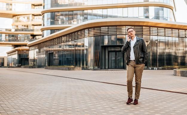 Bel homme avec des lunettes avec un smartphone dans la rue d'une grande ville. homme d'affaires parlant au téléphone sur fond urbain